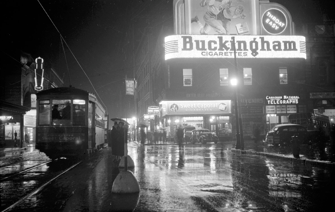 Nightscape. A streetcar passes a building with a neon sign advertising Buckingham cigarettes.