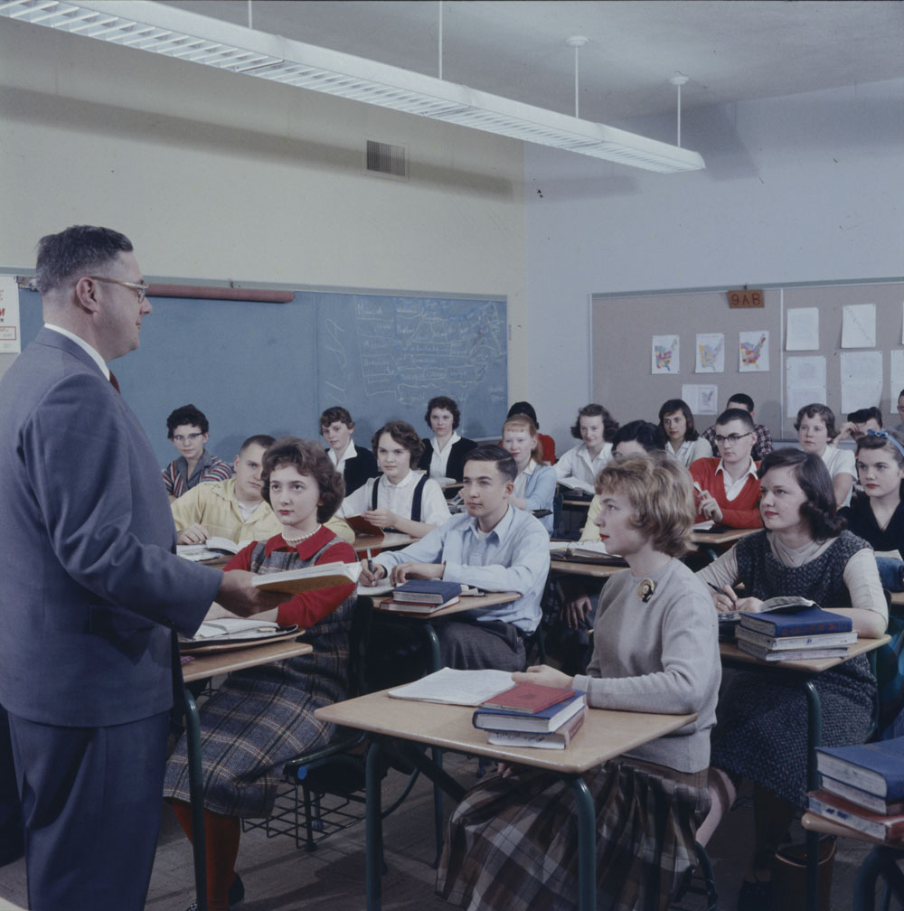 A man in a suit presides over a classroom full of attentive teenagers.