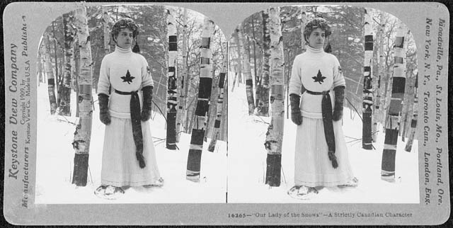 A woman in a sweater with a maple leaf, a long skirt and a toque stands in a snowy birch forest.