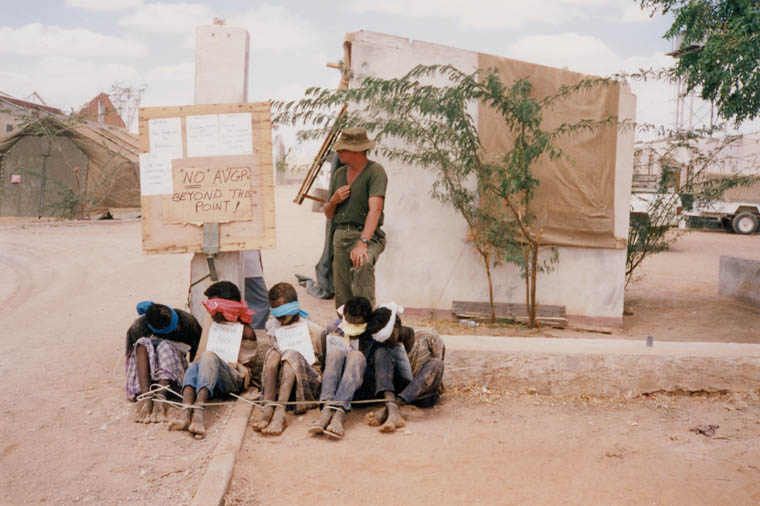 A soldier stands behind four boys, blindfolded and bound together. They sit on packed dirt.