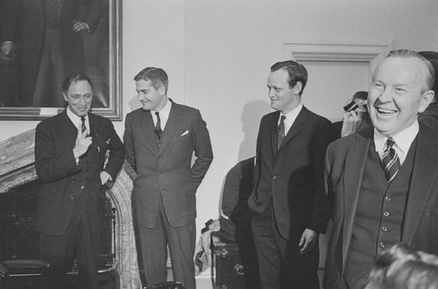 Four smiling men in suits stand in a room with white walls. An ornate portrait hangs behind them.
