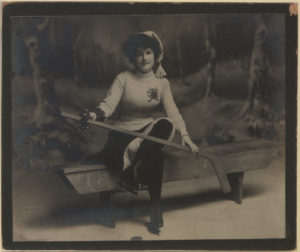 A woman sits on a wooden bench on an ice rink, holding a hockey stick across her knee.
