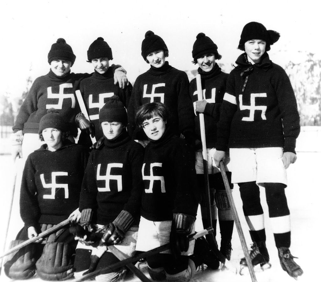 Eight young women wear hockey jerseys adorned with swastikas.
