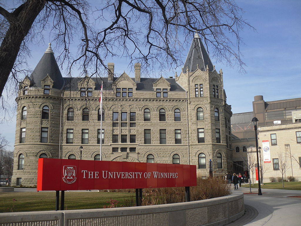 """Sign in front of a stone building that says """"University of Winnipeg."""""""