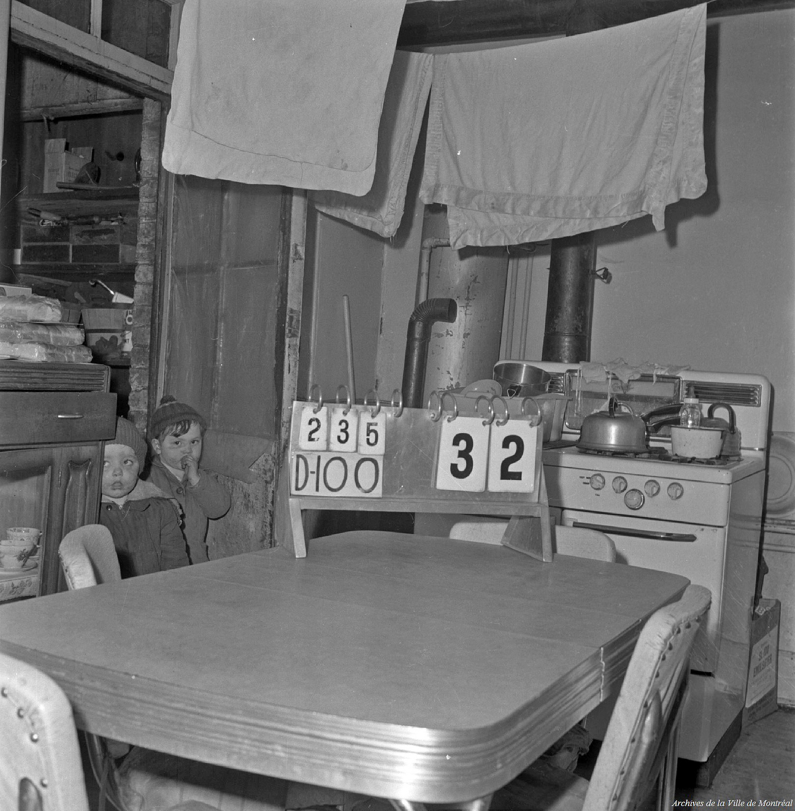Two children stand in a kitchen with blankets hanging on laundry lines.