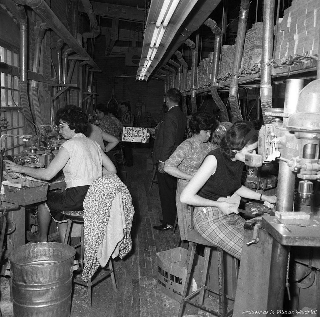 Women work at stations in a factory. One woman's faux leopard coat is over the back of her chair.