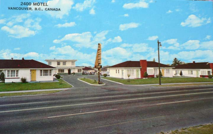 """Several low buildings built close together. At the entrance to the driveway is a """"2400"""" neon sign."""