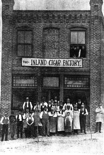 Two dozen workers in longsleeves and aprons stand outside a brick cigar factory.