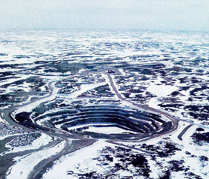 A small pit in a snow-covered field. Roads snake to and from the pit.