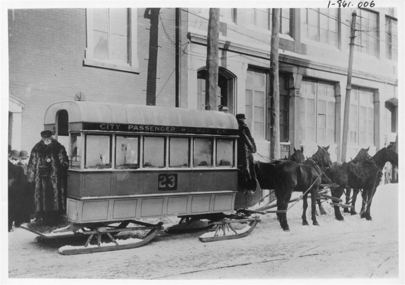 Four horses pull a tram on sled runners in the city.