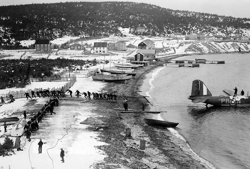 Men pull an airplane out of the sea using ropes. The seaside town is covered in snow.