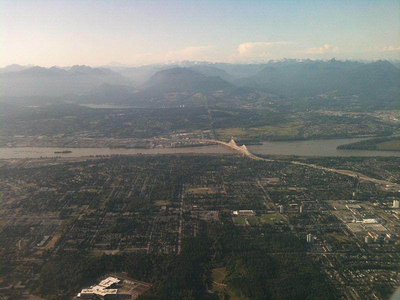 Aerial view of a city. A bridge crosses a river. Mountains are in the distance.