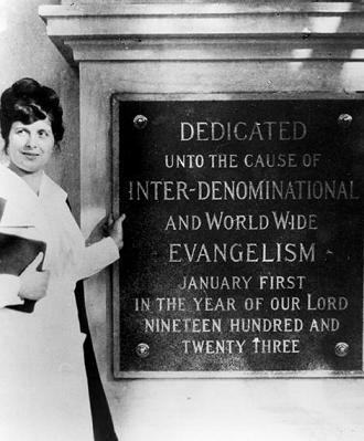 A woman stands by a plaque. Long description available.