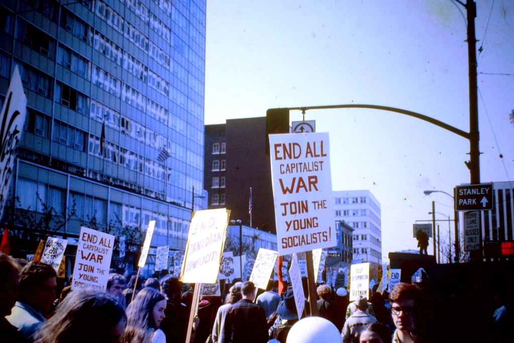 """A protest march. Someone's sign says """"End all capitalist war. Join the young socialists!"""""""