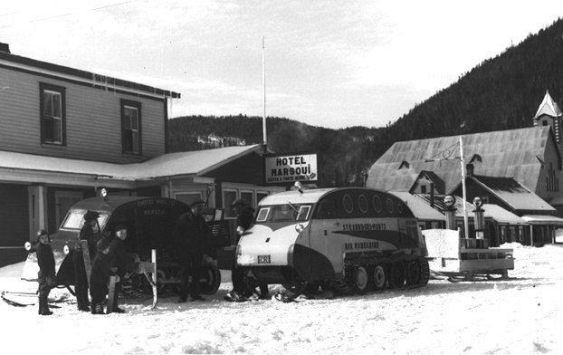 Vehicles with rubber track tires, surrounded by snow.