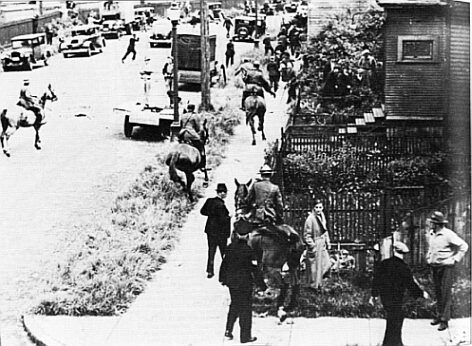Mounted police charge down the street and sidewalk in pursuit of fleeing men.