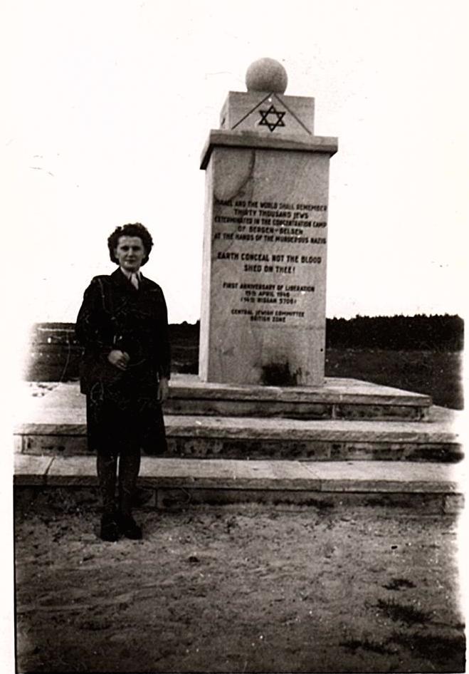 A woman stands by a monument. Long description available.