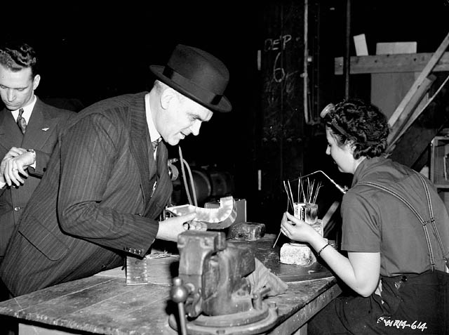 A man in a suit and a fedora inspects a piece of metal with a female factory worker looking on.