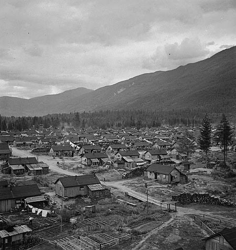 Collection of low buildings at the foot of a mountain, beside a forest.