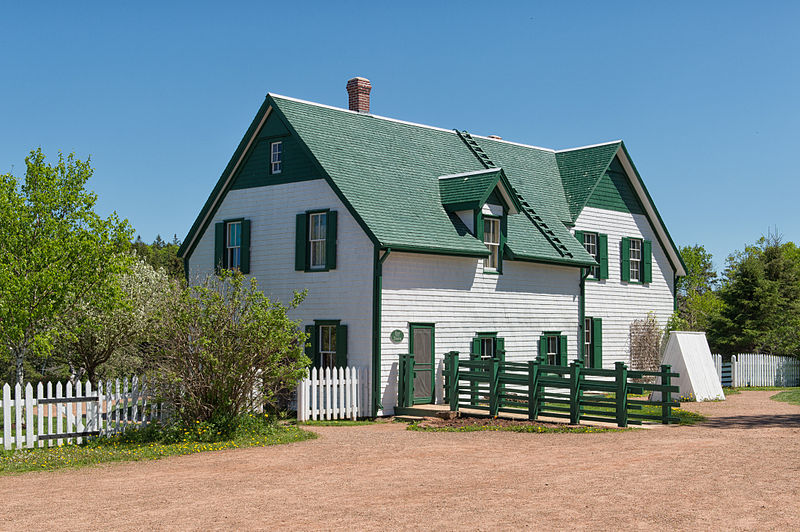 White farmhouse with a green roof and shutters.