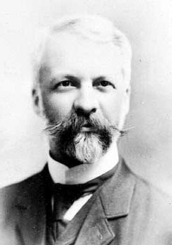 Photo portrait of an older man in a suit with a moustache and a goatee.