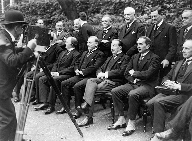 A dozen men in suits sit and stand for a photographer wearing a bowler hat.