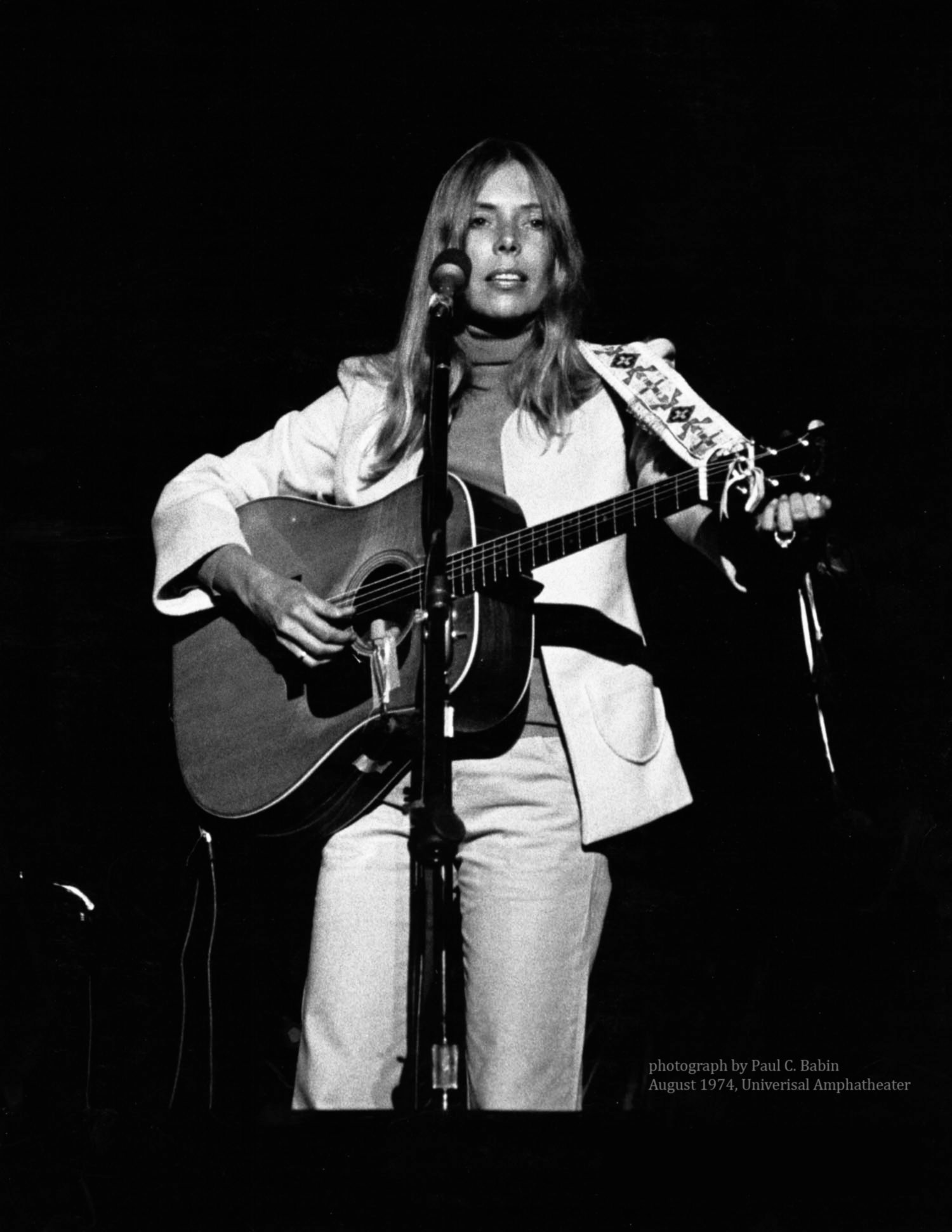 A woman stands at a microphone, holding an acoustic guitar. She wears a turtleneck and a blazer.