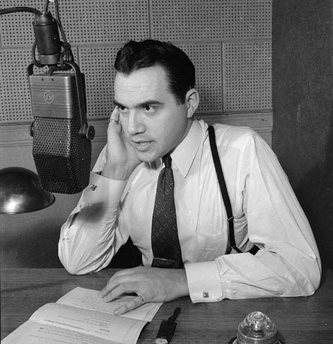 A man in a wearing suspenders holds a hand to his ear and talks into a broadcast microphone.
