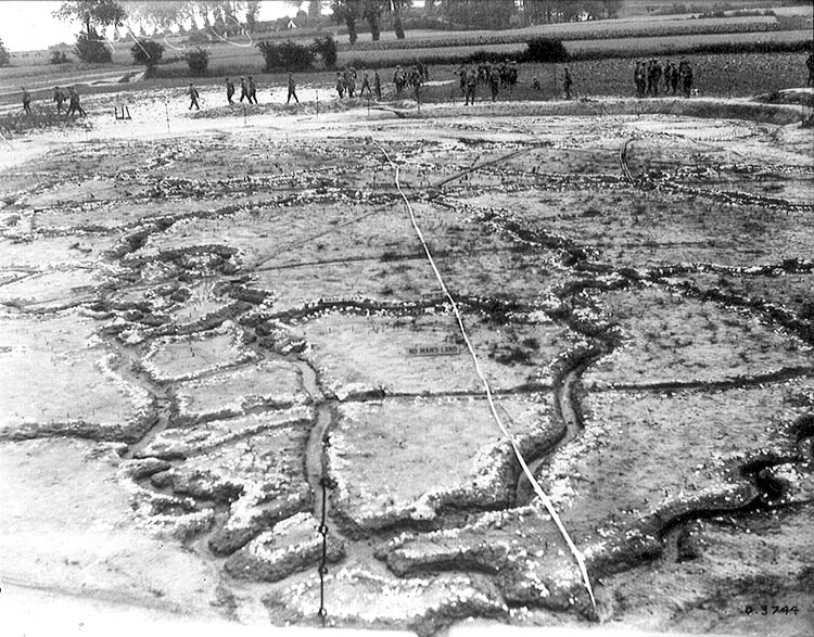 Lines drawn in a muddy field to represent trenches. Soldiers walk past.
