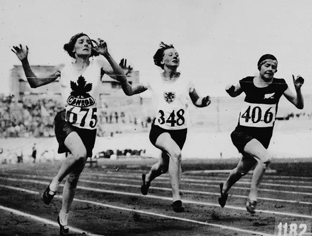 Three young women hurtle down a running track, arms raised, faces strained.