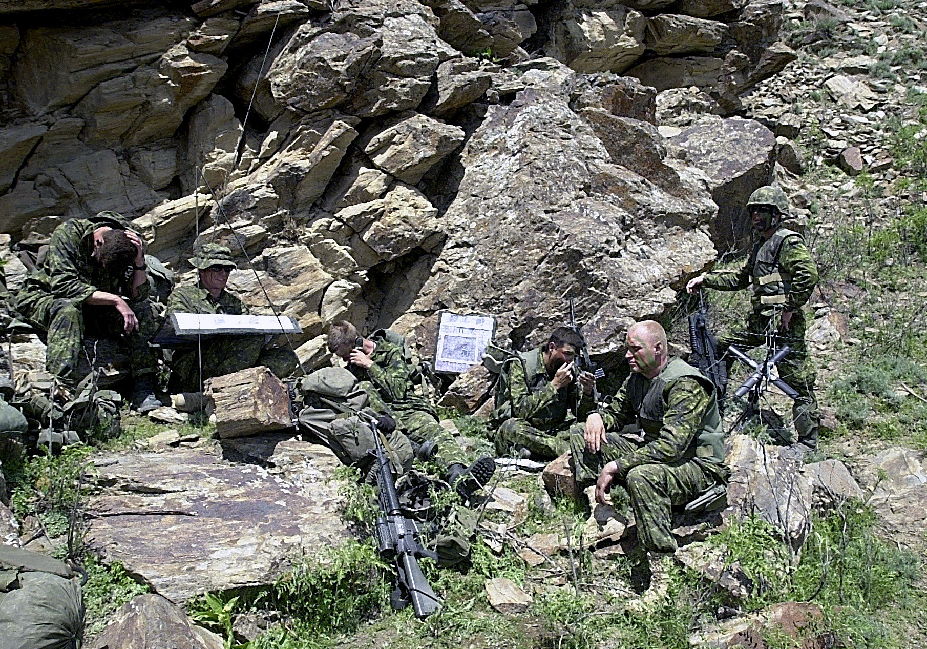 Camouflaged soldiers sit outside a cave. They hold guns and wait for something.