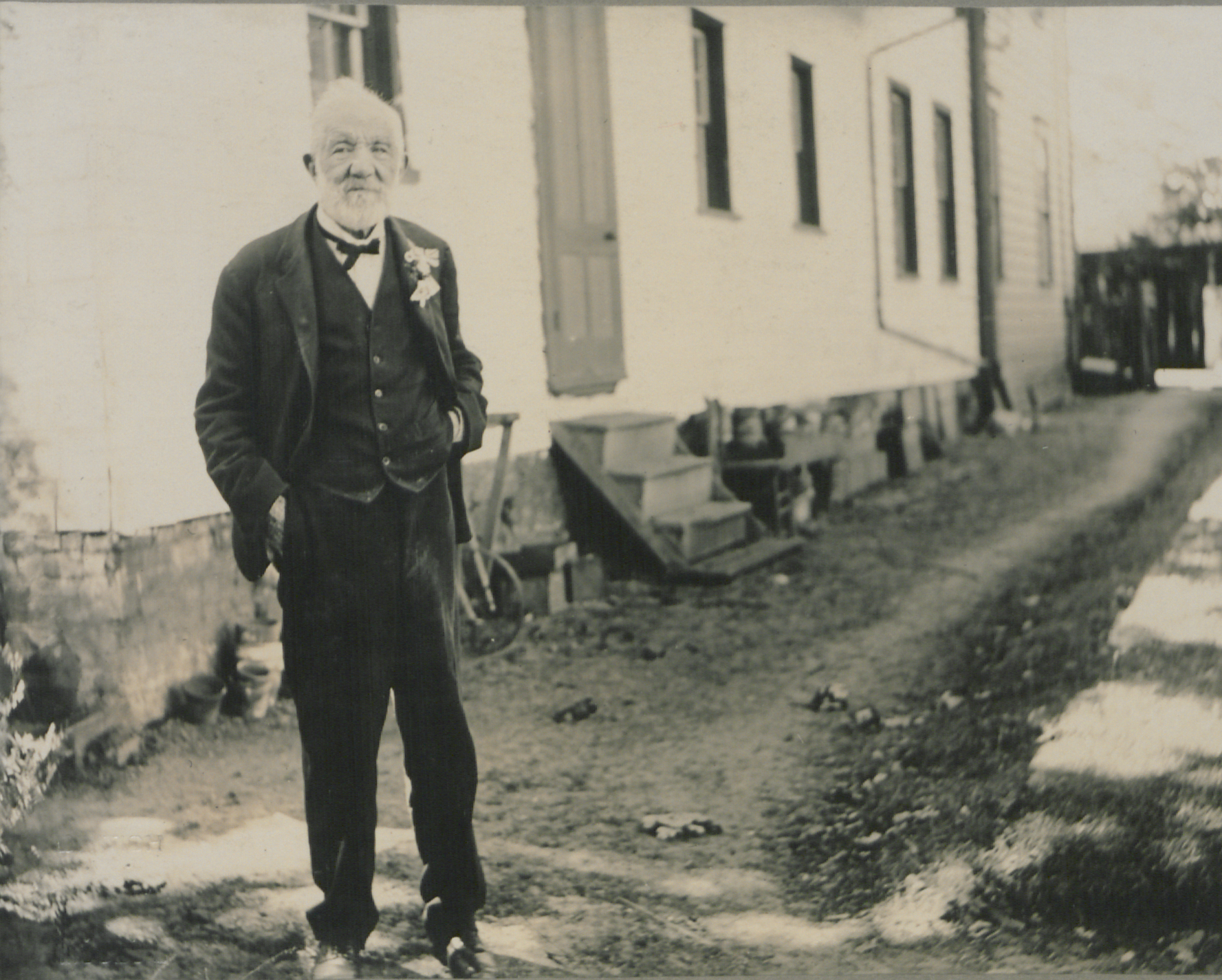Old man in a suit stands outside a house on a dirt road.