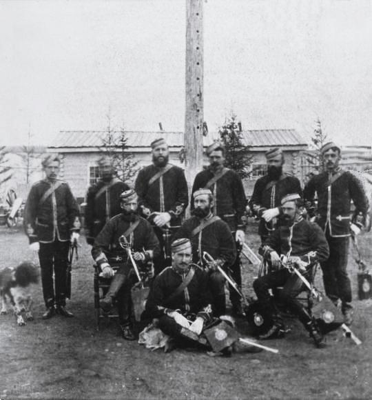 Ten men in jackets, boots, and pillbox hats. Each has a sword.