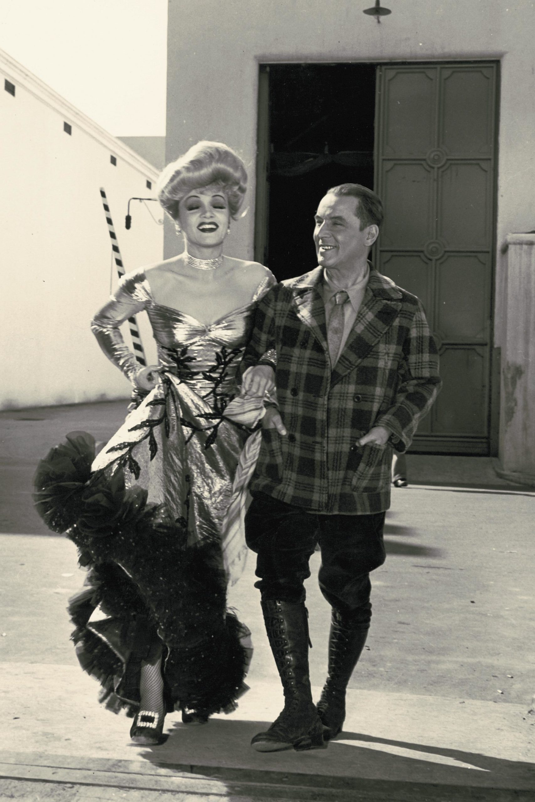 A man in a plaid blazer smiles at a woman in a glamorous dress.