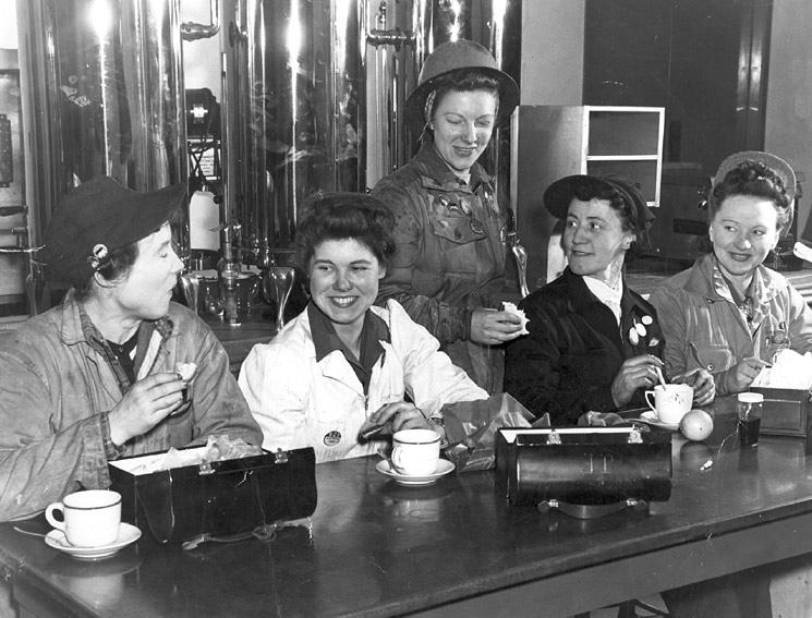 Five women in industrial uniforms sit and eat lunch out of metal lunchboxes.