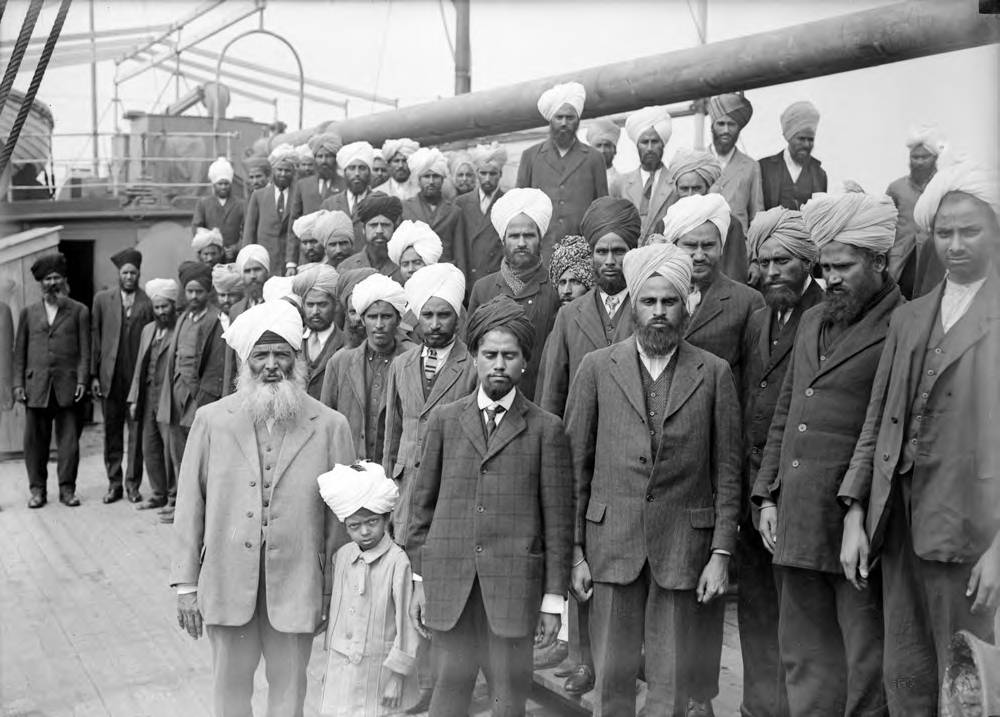 Forty men in suits and turbans stand on the deck of a ship.