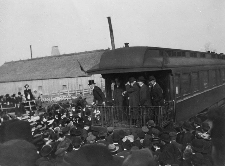 A crowd gathered around a railway car. Five men stand on the platform of the observation car.