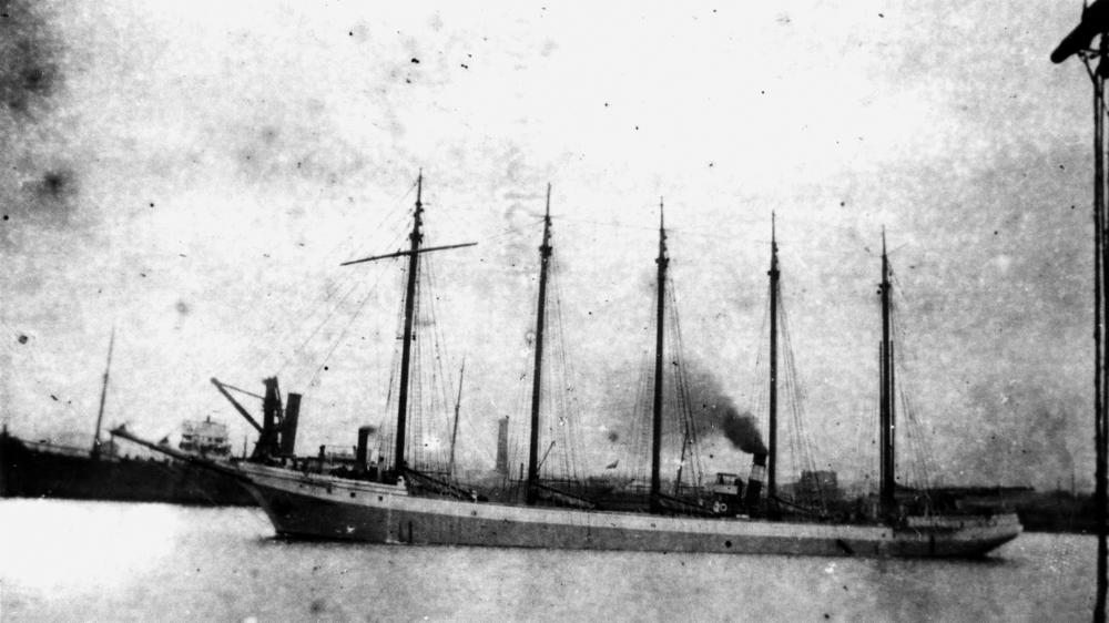 A long sail and steam combination ship near harbour.