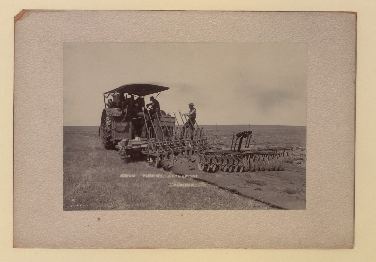 Two men operate a tractor on a field.