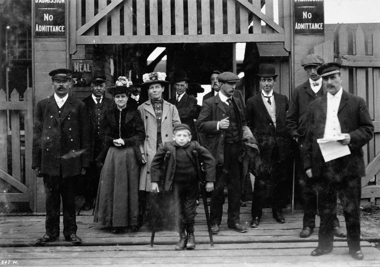 Eight men, two women, and a boy stand in front of a tall wooden gate.