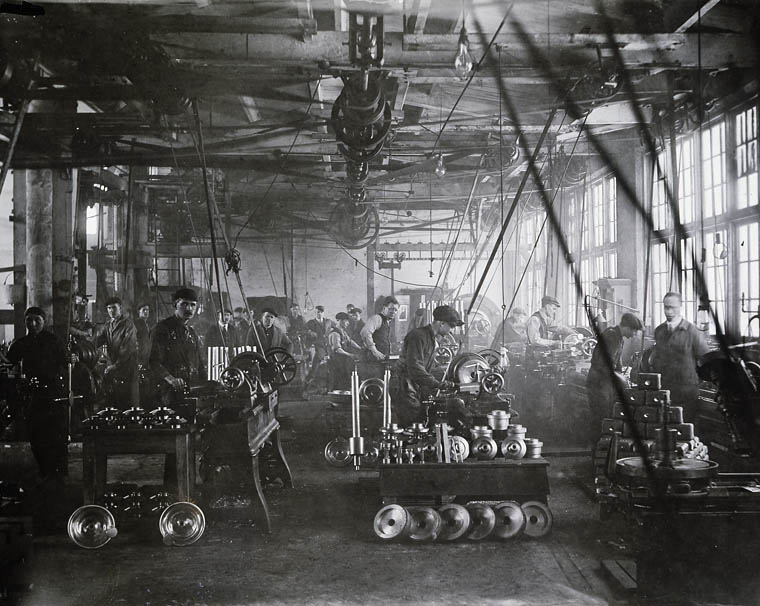 Men work with machines on a factory floor.