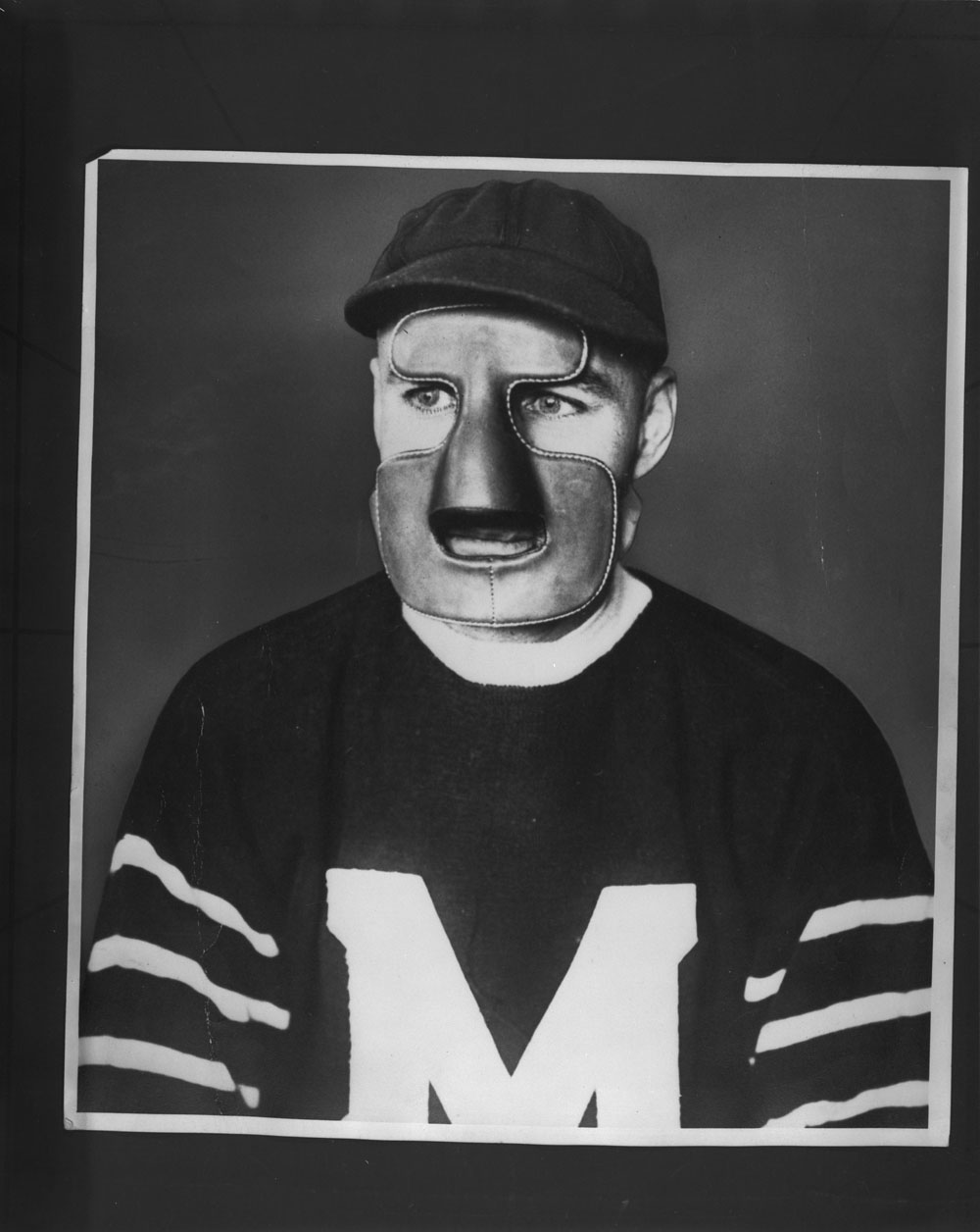 Man wearing a hockey jersey and a mask that covers his forehead, nose, chin, and lower cheeks.