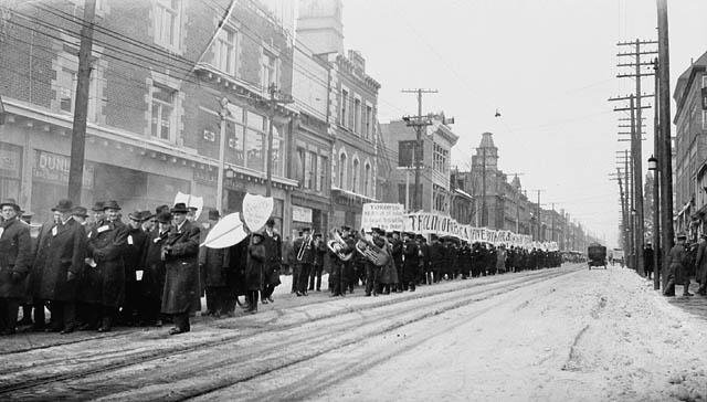Men march down street carrying signs. Many wear overcoats and hats. Some carry musical instruments.