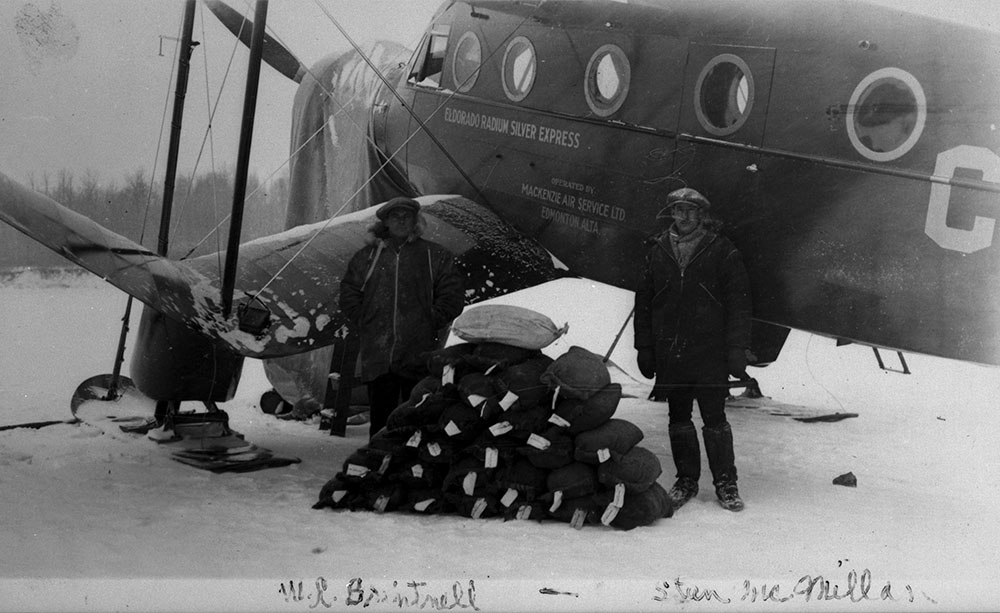 Two men stand beside a waist-high pile of small sacks. Behind them is an airplane.