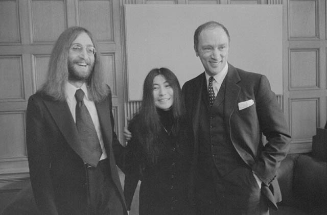 A man with long hair poses beside a Japanese woman. A man grins and has his arm around the woman.