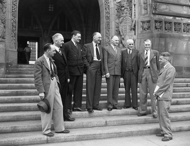 8 men in suits stand in a semicircle on the stone steps of a building, looking at the rightmost man.