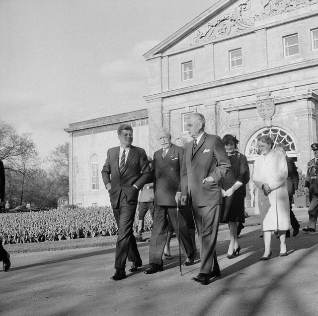 Three men in suits walk down a path. Two women follow them. In the background is a grand house.