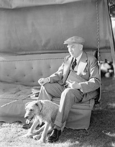 A middle-aged man wearing a suit sits on an outdoor couch with a terrier at his feet.