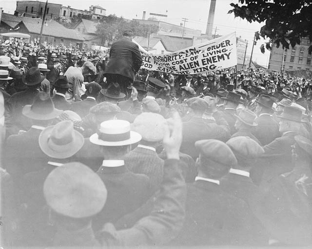 Shot from the back of a crowd of protesters. A banner is lifted above the crowd.
