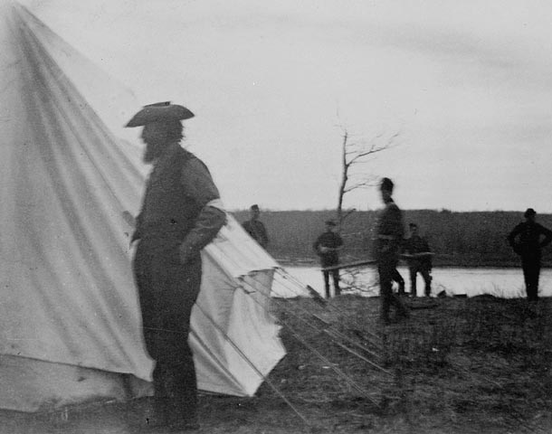 Riel standing in front of a tent by a river.